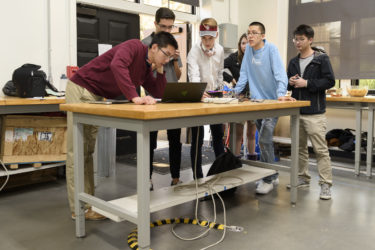 Students test each other's devices at the freshman haptics class open house.