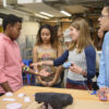 Senior Moses Swai, left, gets a demonstration from Jabreea Johnson, Charlotte Peale, and Johnny Armenta who developed a Foot Haptic device.
