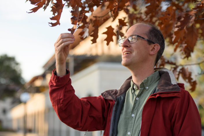Alex Dunn stands under a tree and examines a leaf.