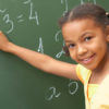 happy girl doing math at chalkboard