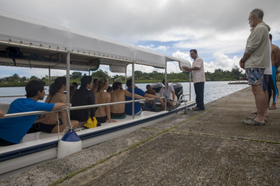 The president of Palau standing by a boat of students