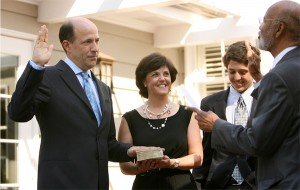 John Roos is sworn in by Judge Thelton Henderson while Roos's wife, Susan, and son David look on.