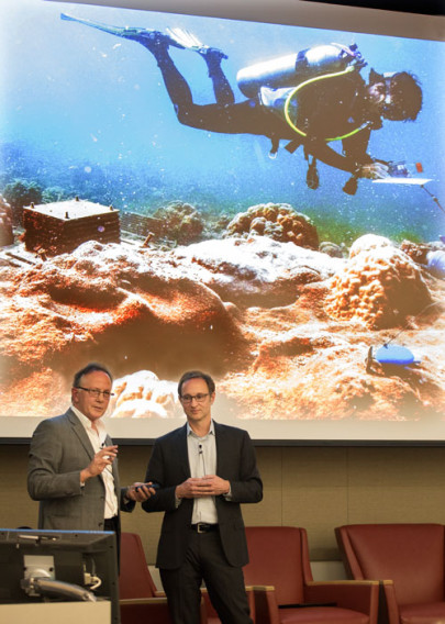 Steve Ringman and Craig Welch standing infront of a screen that is showing a photo of a man scuba diving.