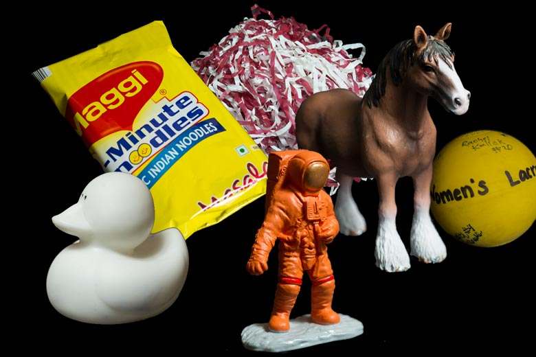A collage of items including  a Cardinal and white pon pon; a bag of Indian noodles, a white rubber ducky; a women's lacrosse ball; a plasitc horse and a toy astronaut