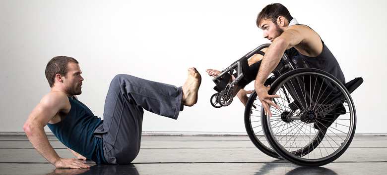man on floor and man in wheelchair facing off