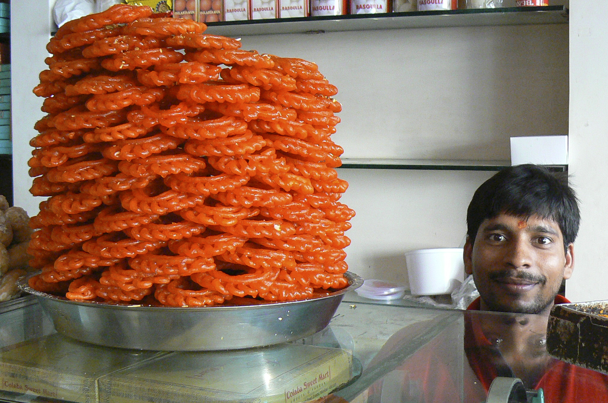 "Candy Man: ""This picture was taken in the neighborhood of Colaba in Mumbai, India, in a candy shop. The reason I like this picture so much is because of the dominant role the candies play in the overall composition, symbolically reflecting some of what India can offer (or at least what the West captures at first glance) – taste, color, smell and hospitality. All big and extravagant. The twisted reflection of the smiley candy man's face completes this image, calling us to revisit our initial – Western – premises."" -- Ravid Itay (Handa Center)"