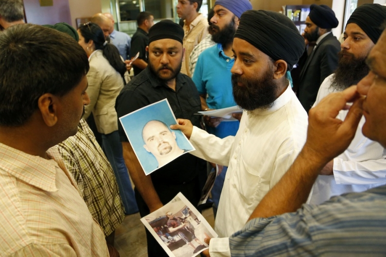 Members of Wisconsin's Sikh community look at a mug shot of Wade Michael Page / Photo by Getty Images