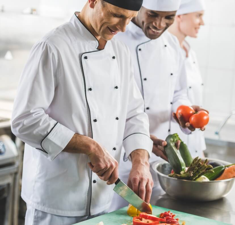 Chef sliding fresh ingredients into a pan