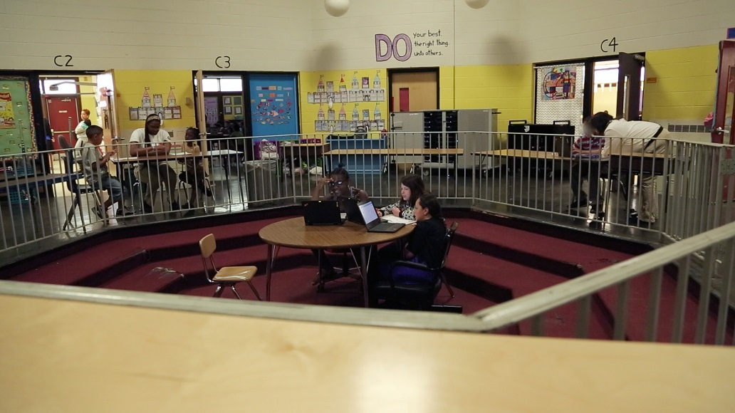 This photo shows a large, indoor, open space being used simultaneously for two small instructional groups and a one-on-one session.
