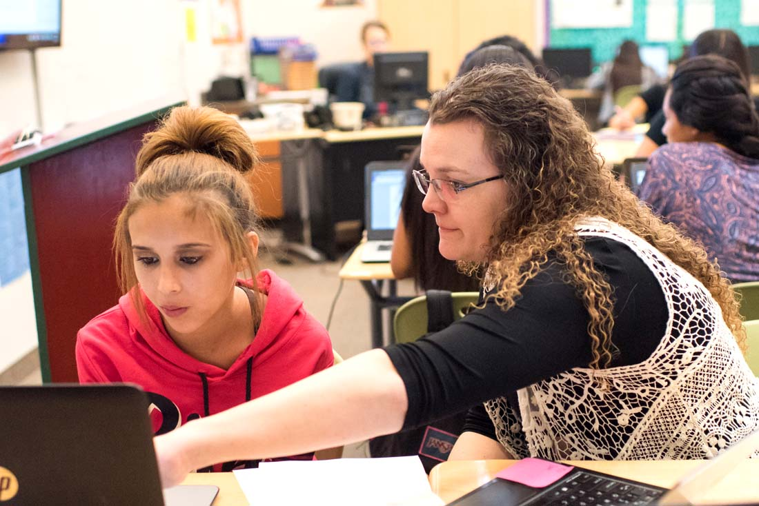 teacher and student look at a laptop screen