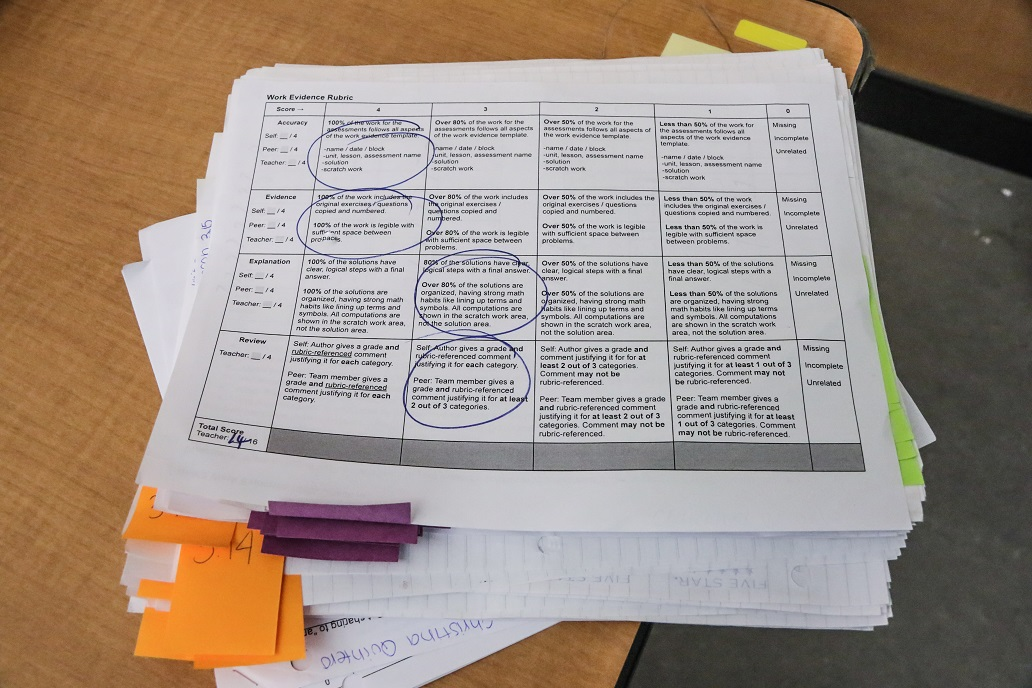 This photo shows a teacher grading a worksheet.