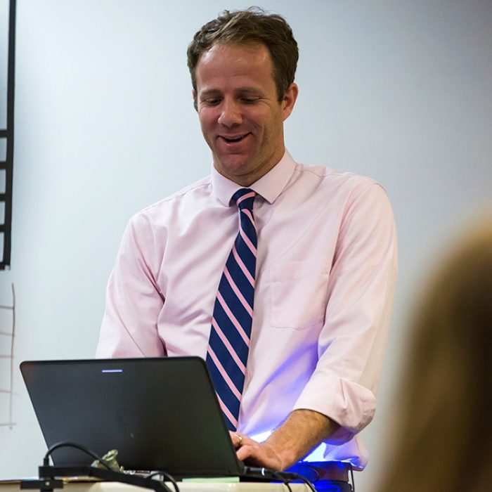 Teacher looks down at laptop, standing and smiling, at front of room