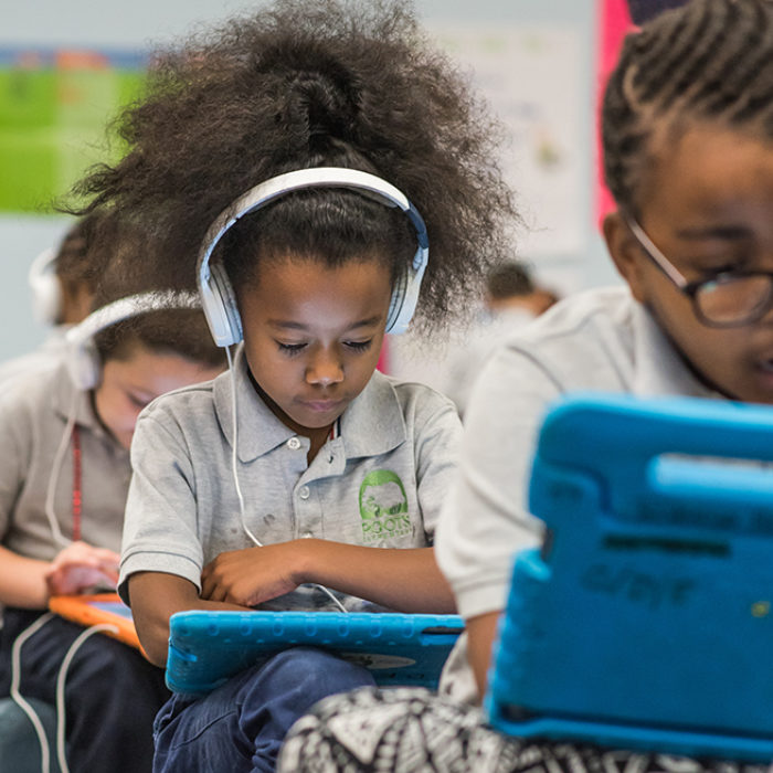 Students using tablets sit in row, wearing headphones