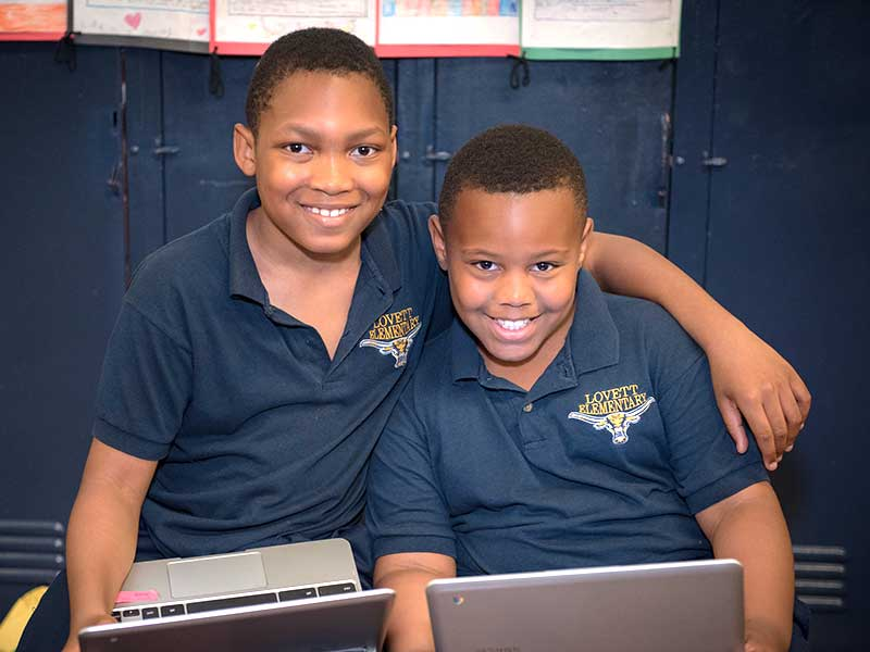 One male student in a school uniform sits with his arm wrapped around the shoulders of another male student in a school uniform, both holding laptops