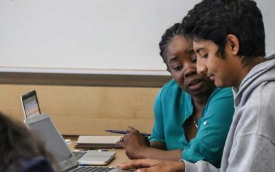 Photo of student and teacher working together seated at a table in front of a laptop