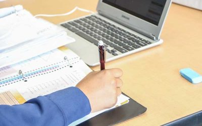 Photo of student arm writing in notebook with laptop in background