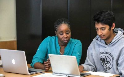 Photo of teacher and student working side by side at table with laptops directly in front of them