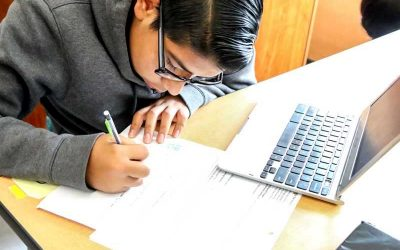 Photo of student working at table writing on worksheets with laptop in front of him