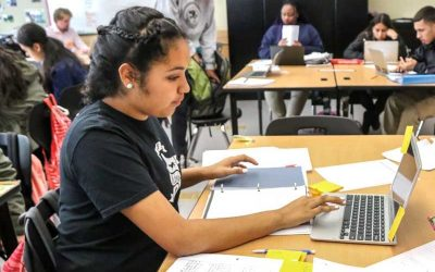 Photo of seated student working with her notebook and on her laptop