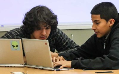Photo of two students working together in front of laptop