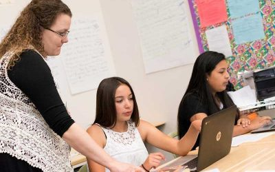 Photo of teacher standing and speaking with seated student working on her laptop