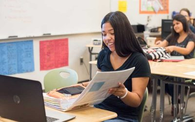 Photo of student viewing her binder with laptop in front