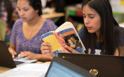 Photo of student reading Shakespeare with another student in background