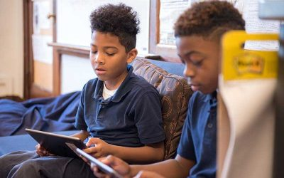 Two students sit on couch, reading from tablets
