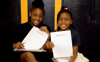 Two students sit beside each other in hallway and hold up reports, smiling