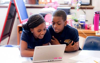 Two students work inside classroom, looking at laptop together