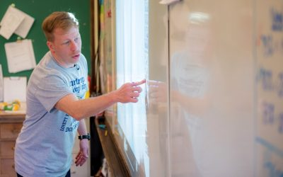 Teacher stands in front of interactive white board, pointing at the screen