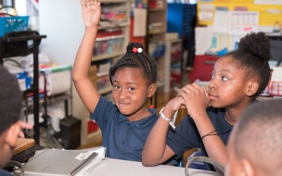 Two female students sit at desk in classroom as one raises her hand