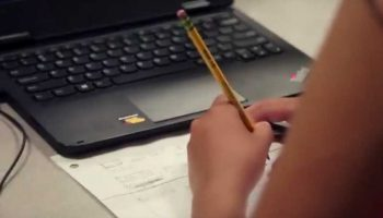 Photo closeup of student working in notebook with laptop on desk