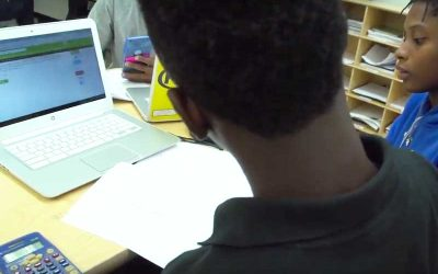 Photo of students working together with notebook and devices