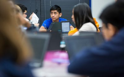 Students sit grouped at tables with technology