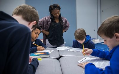Teacher looks on as students complete work at desk