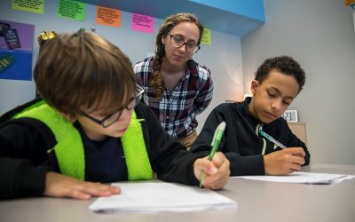 Teacher looks over the shoulders of two students as they work