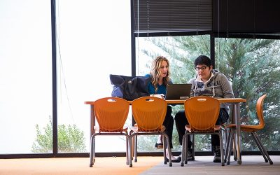 Teacher sits at table with student with windows in background, looking together at laptop