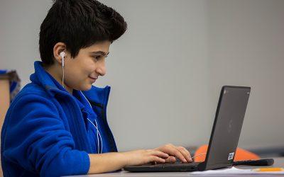 Student wearing earphones smiles as he works on laptop