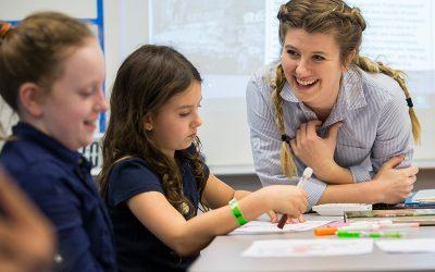 Teacher smiles as she talks with a student