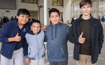 Four students stand in line, two give thumbs up to camera