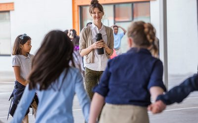 Teacher stands in front of a line of students holding hands