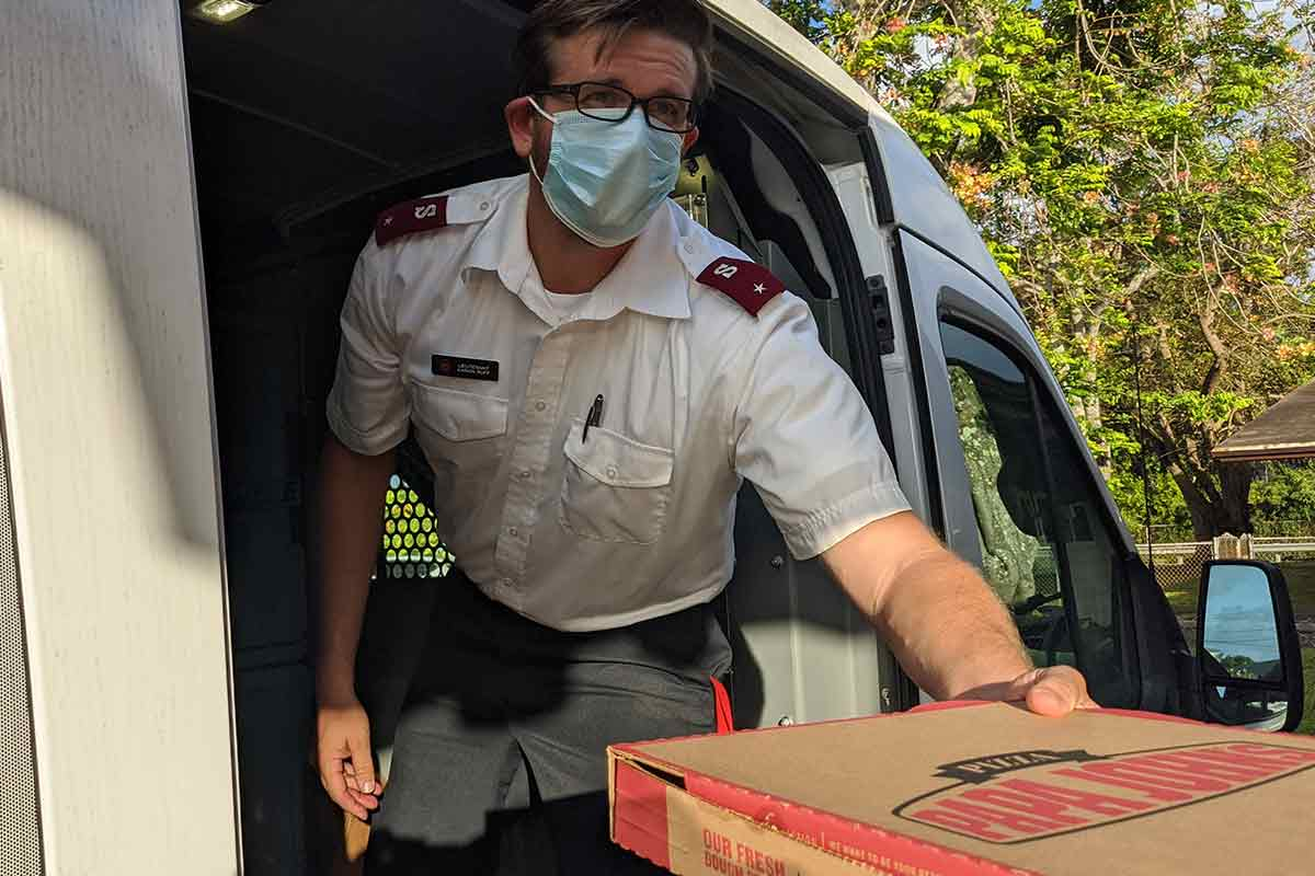 salvation-army-officer-handing-out-pizza