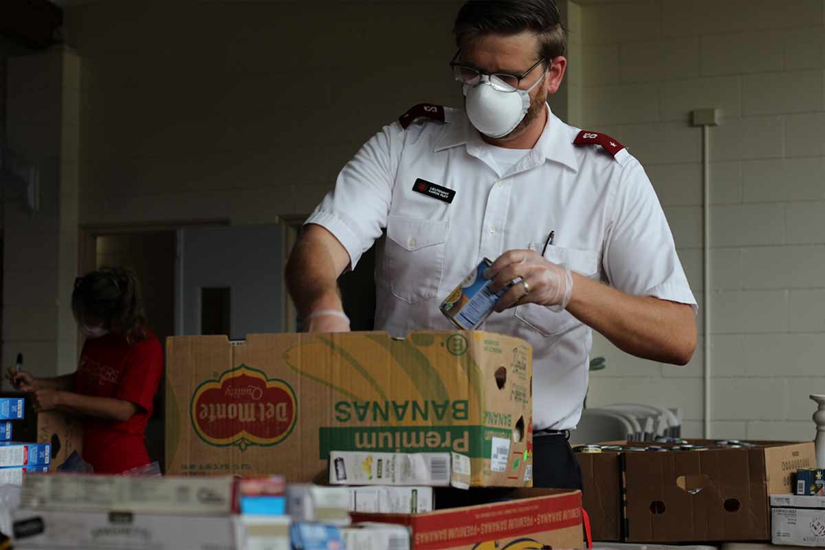 officer packing food basket covid relief