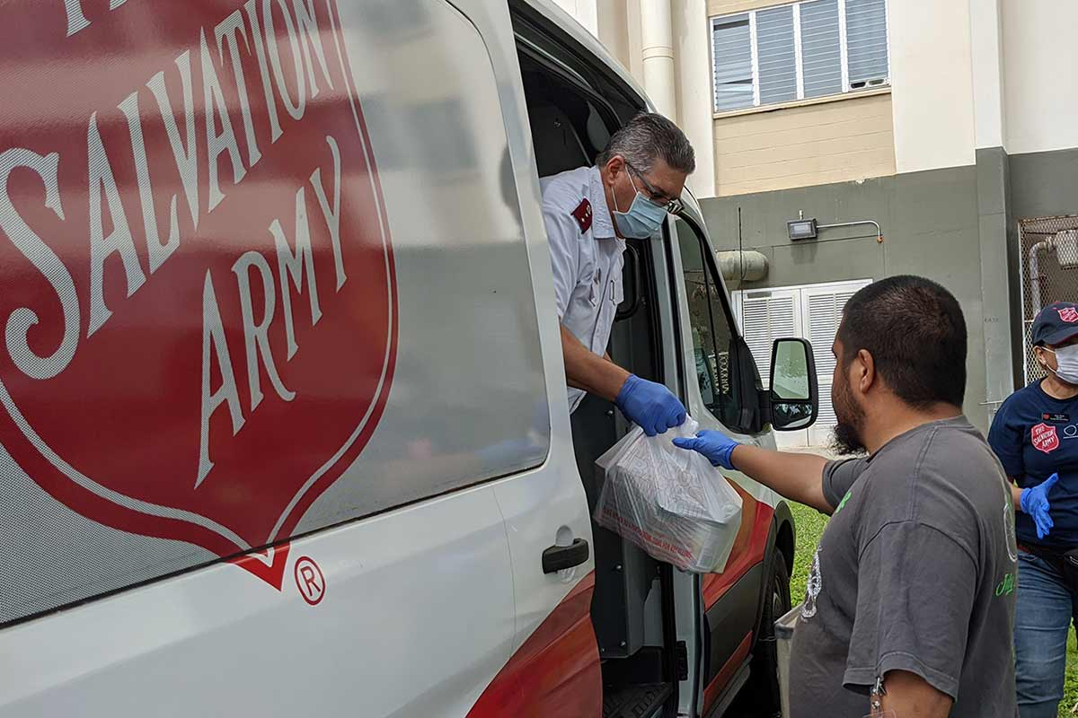 Salvation Army staff handing out food bags at Kuhio Park Terrace amid COVID-19 Pandemic