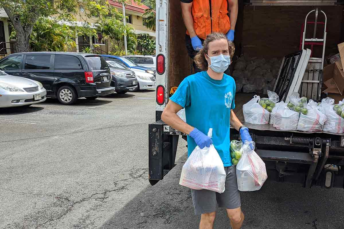 Salvation Army volunteer carrying bags of food to Palolo Homes Residents