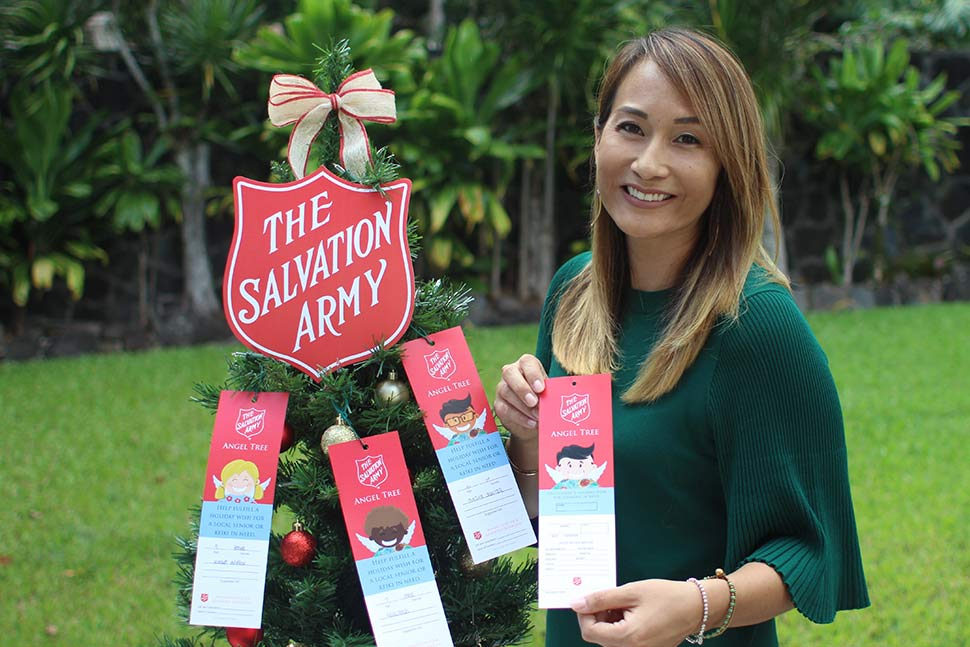 mari holding angel tag in front of angel tree salvation army hawaii
