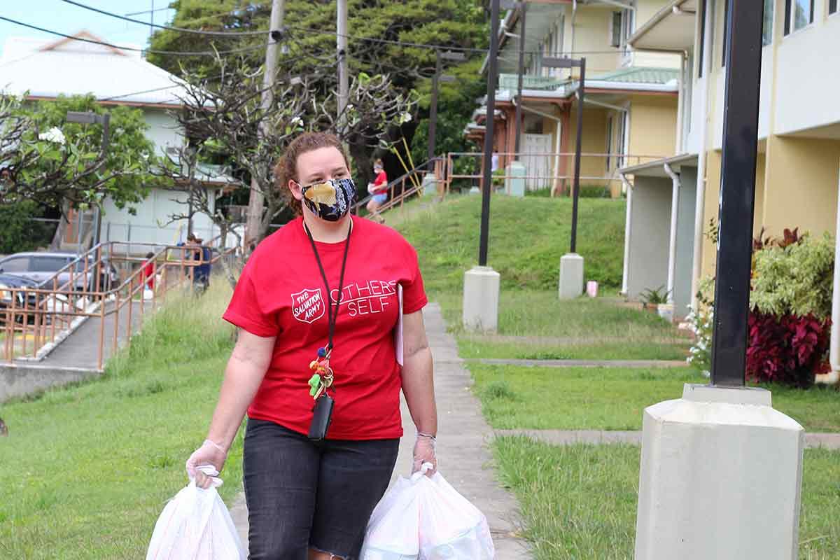 volunteers carrying bags of food to homes in Kalihi