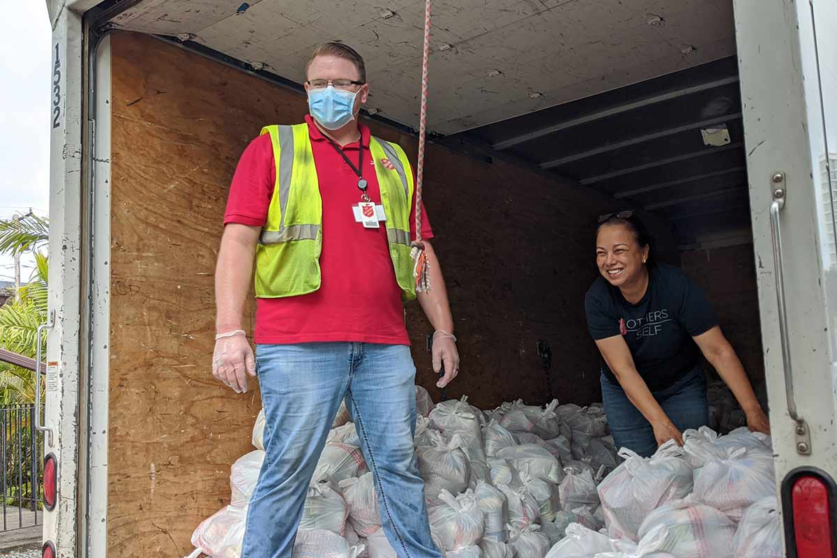 Salvation Army staff with truckload of food bags