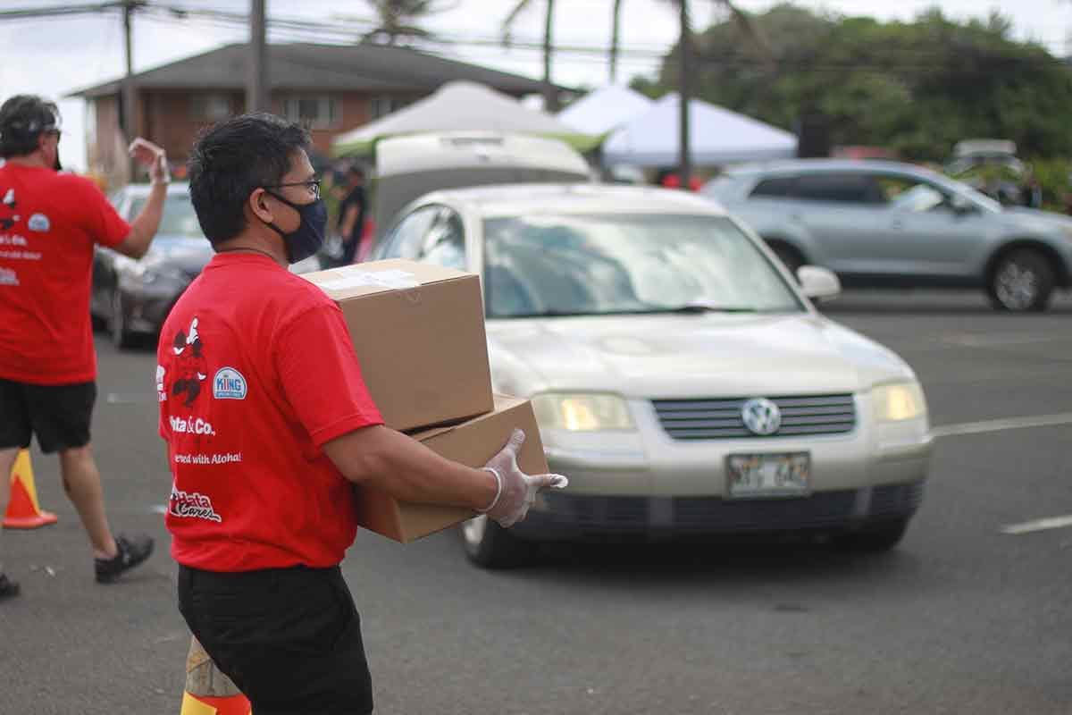 salvation army and y hata volunteer holding food boxes at COVID-19 relief food distribution